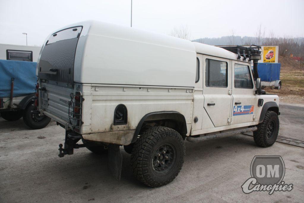Land Rover Defender 130CC s nástavbou OM Canopies model Worker. Defender je jeden opravdu z mála čistokrevných offroadů. Všechno se řadí manuálně-žádné čudlíky a mačkátka, nesmysly, které většinou nefungují. Fuj..